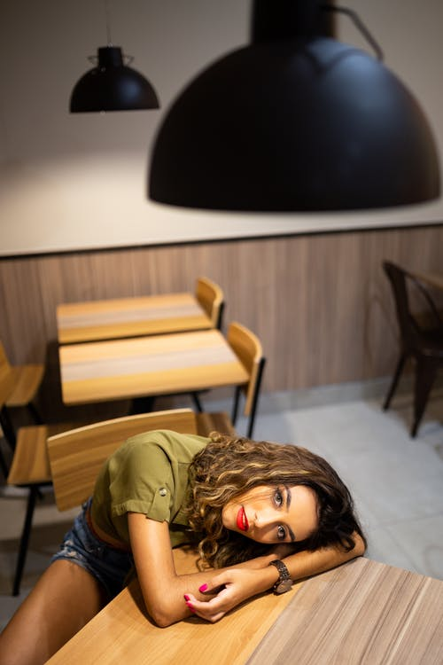 High Angle Photo of Woman Leaning on Table