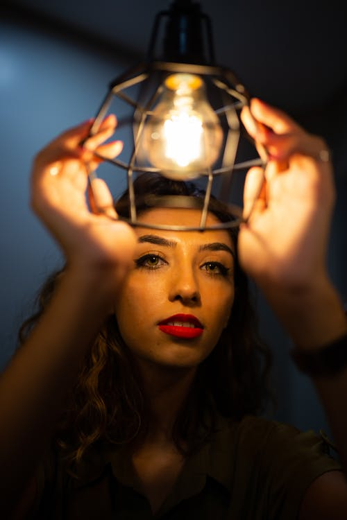 Photo of Woman Holding Lighted Bulb