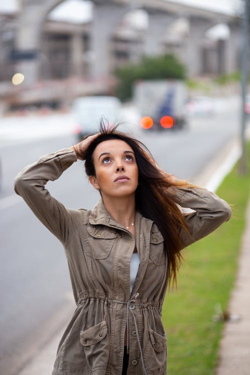 Photo of Woman Holding Her Hair While Looking Upwards