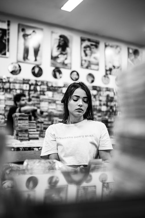 Monochrome Photography of Woman in Music Store