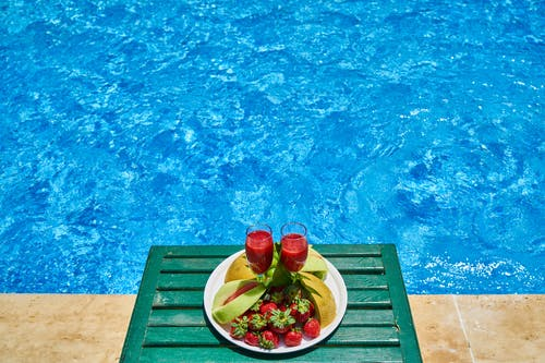 Two Glasses of Drink and Plate of Fruits by the Swimming Pool