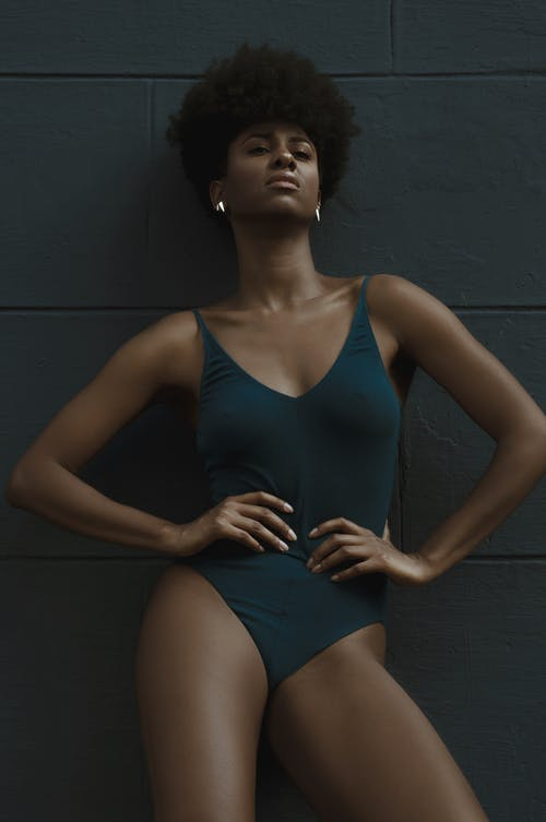 Woman Leaning Against Wall Wearing One-piece Swimsuit
