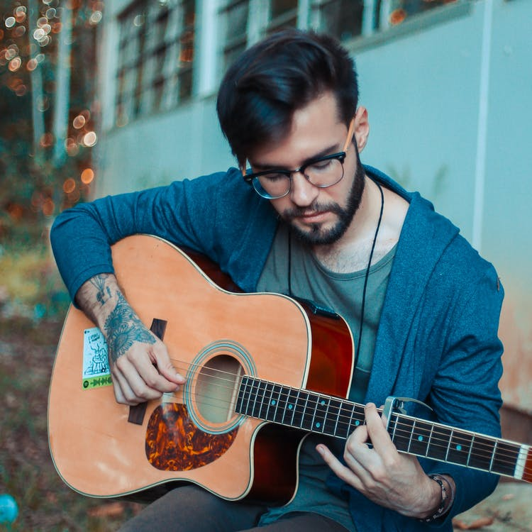 Photo of Man Playing Acoustic Guitar