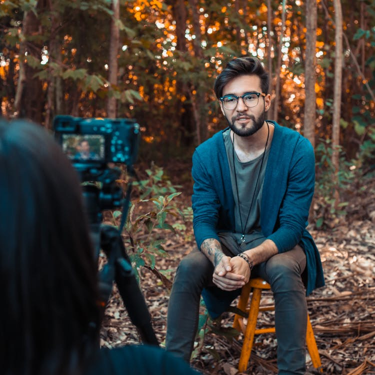 Photo of a Man Sitting in Front of a Camera
