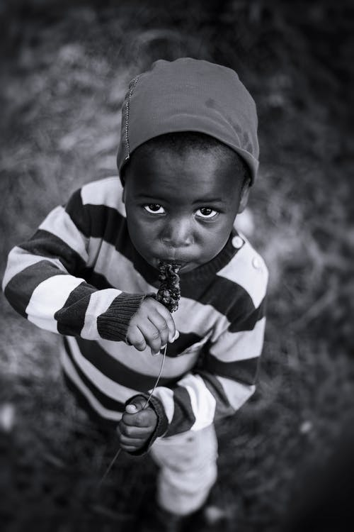 Monochrome Photo of Kid Eating
