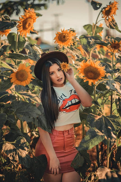 Photo of Woman Wearing White Shirt While Standing Near Sunflowers