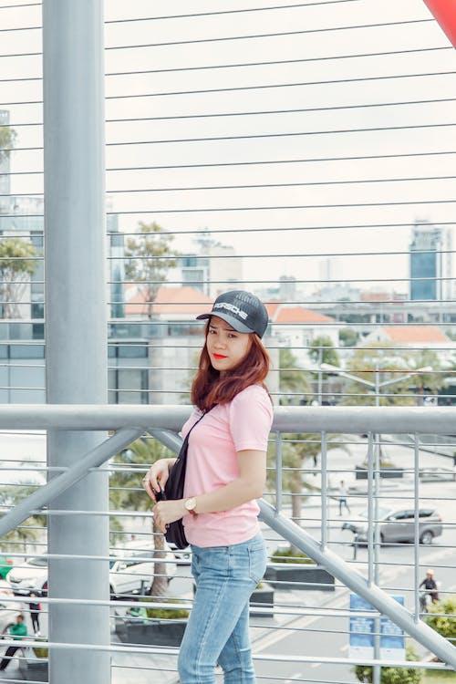 Photos gratuites de balustrade, belle femme, casquette, chemise rose