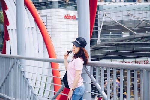 Darmowe zdjęcie z galerii z azjatka, balustrady, czapka z daszkiem, czerwone usta