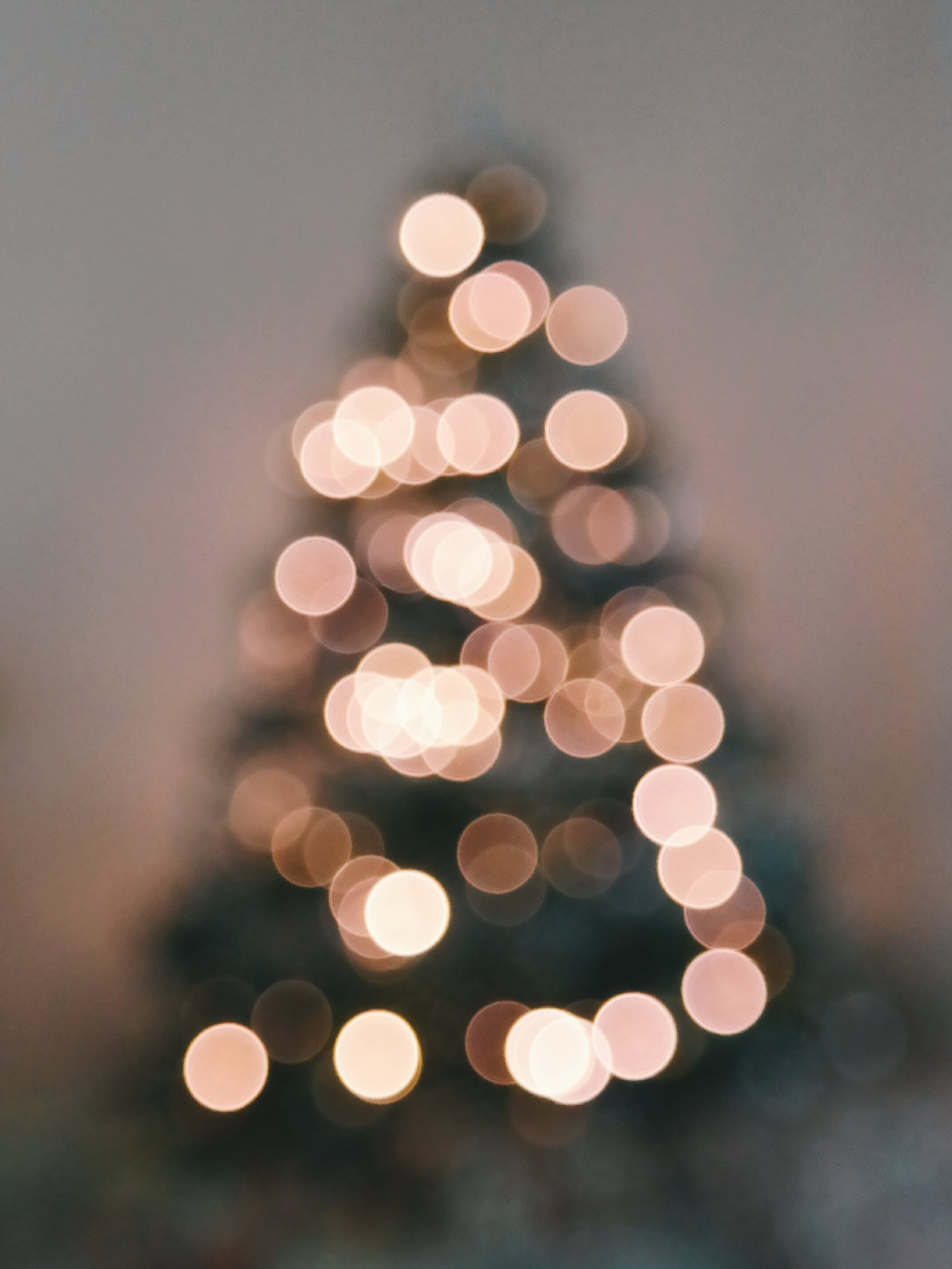 Defocused Image of Illuminated Christmas Tree Against Sky