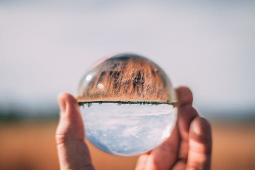 Close-Up Photo of Person Holding Lensball