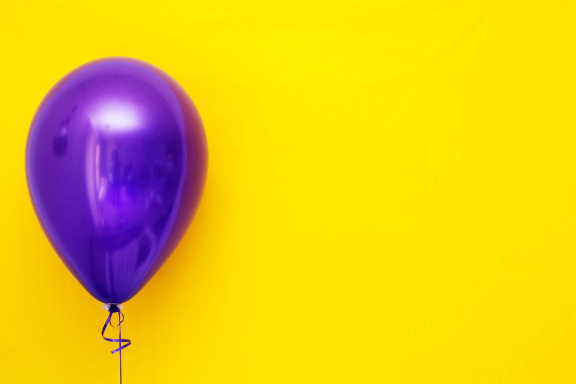Purple Balloon against Yellow Background