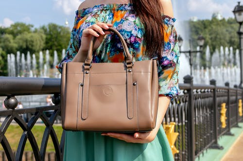Photo of Person Holding Brown Leather Handbag