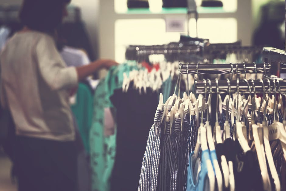 Selective focus photo of clothes on clothing rack