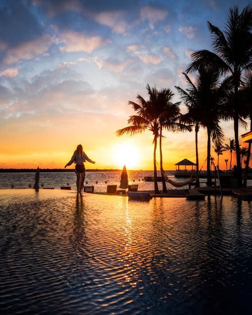 Photo of a Woman Standing Near the Pool during Sunset