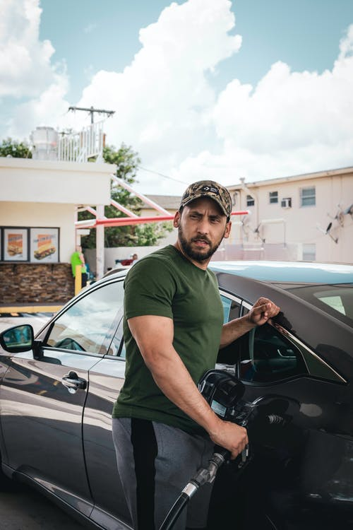 Photo of a  Man Fueling Up His Car