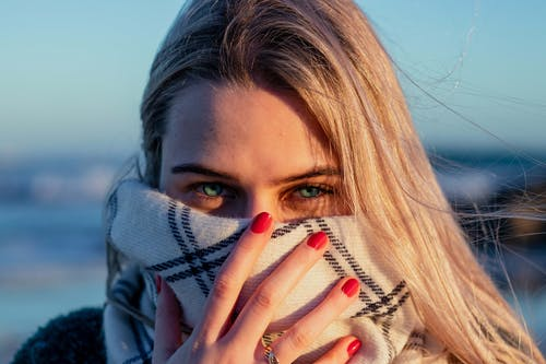 Close-Up Photo of a Woman Covering Her Face With Scarf