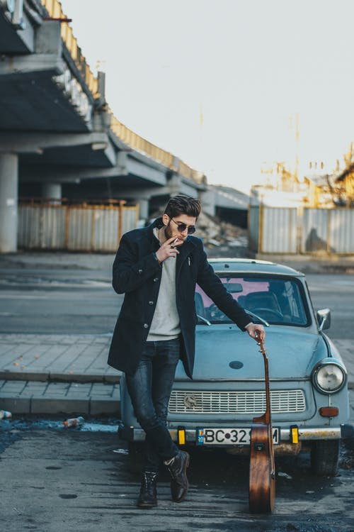 Photo of Man Smoking While Standing in Front of Old Car