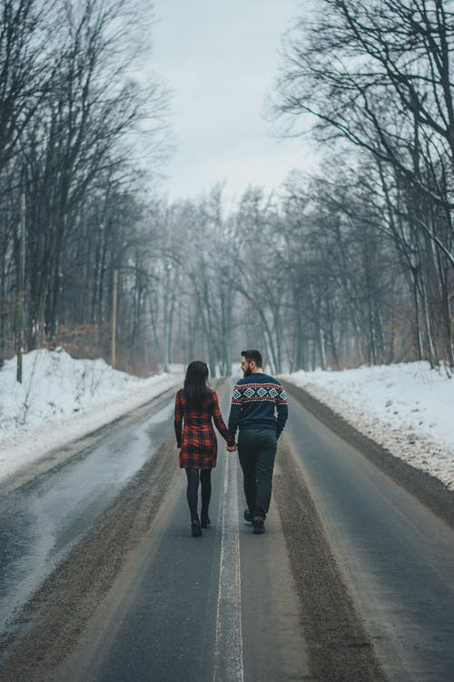 Photo of Couple Walking on Road Near Bare Trees