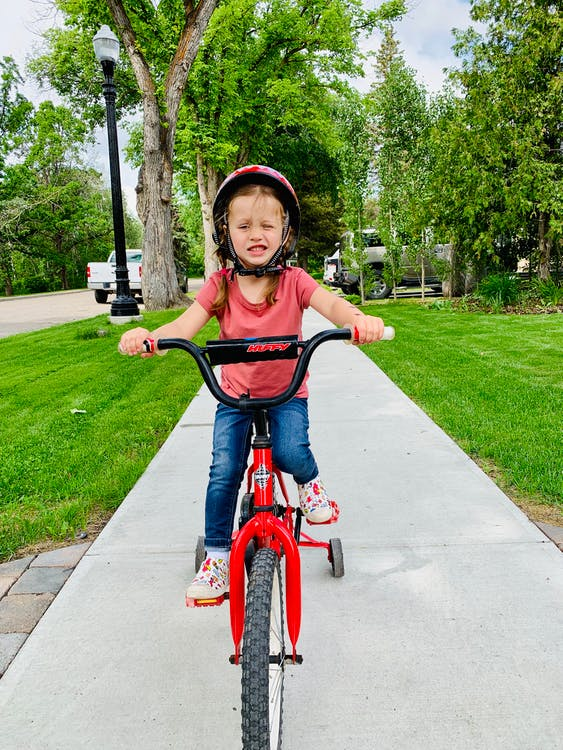 Photo of Young Girl Riding Bike by Sidewalk