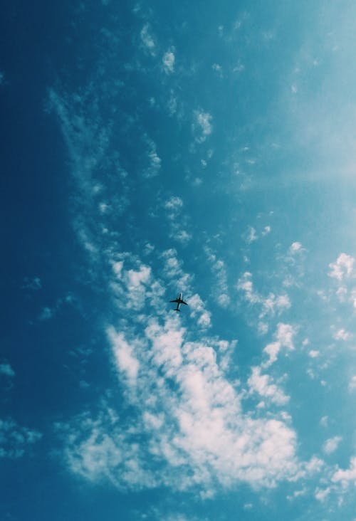 Low Angle Photo of Airplane Flying Under Sky