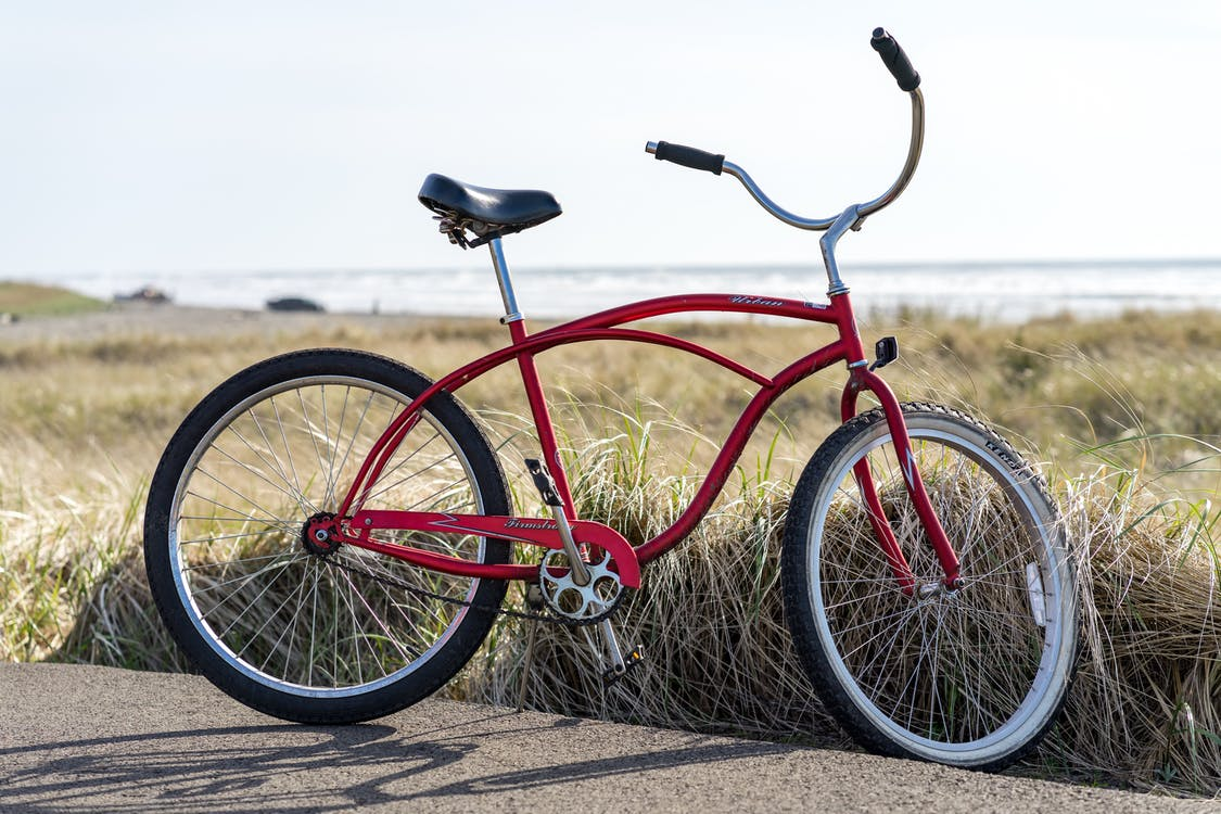 Photo of Red Bike Parked on Road Beside Grass Field