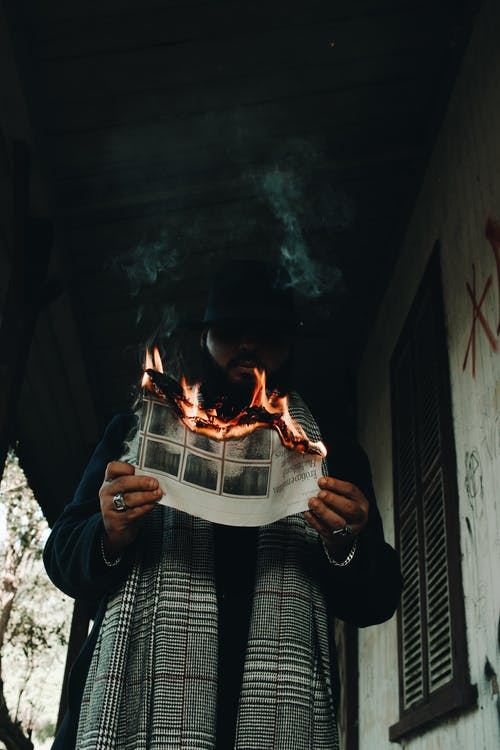 Low-Angle Photo of Man Holding a Burning Paper