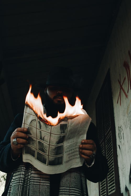 Low-Angle Photo of Man Holding a Burning Newspaper