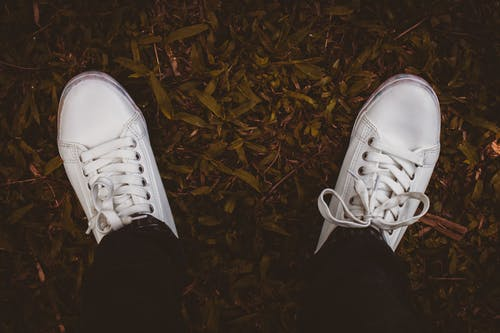 Photo of Person Wearing White Sneakers