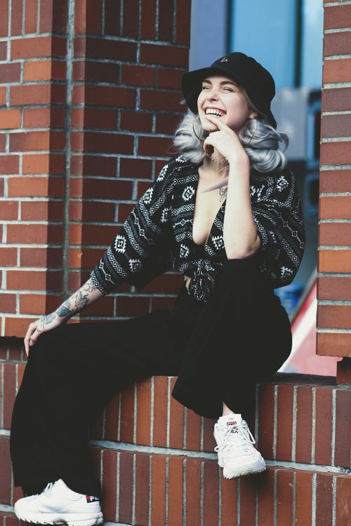 Photo of Laughing Woman with Her Eyes Closed Sitting on Brown Brick Railing