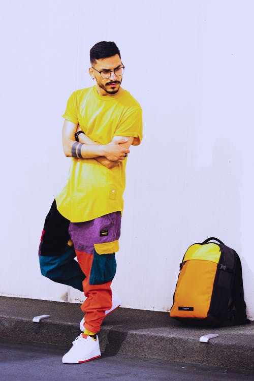 Photo of Man in Yellow T-shirt and Multicolored Pants Posing Beside Backpack Near White Wall