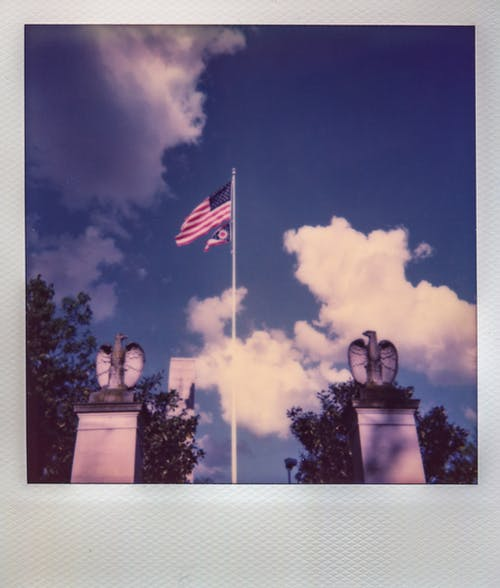 American Flag Flying on Pole Between Two Eagle Statues