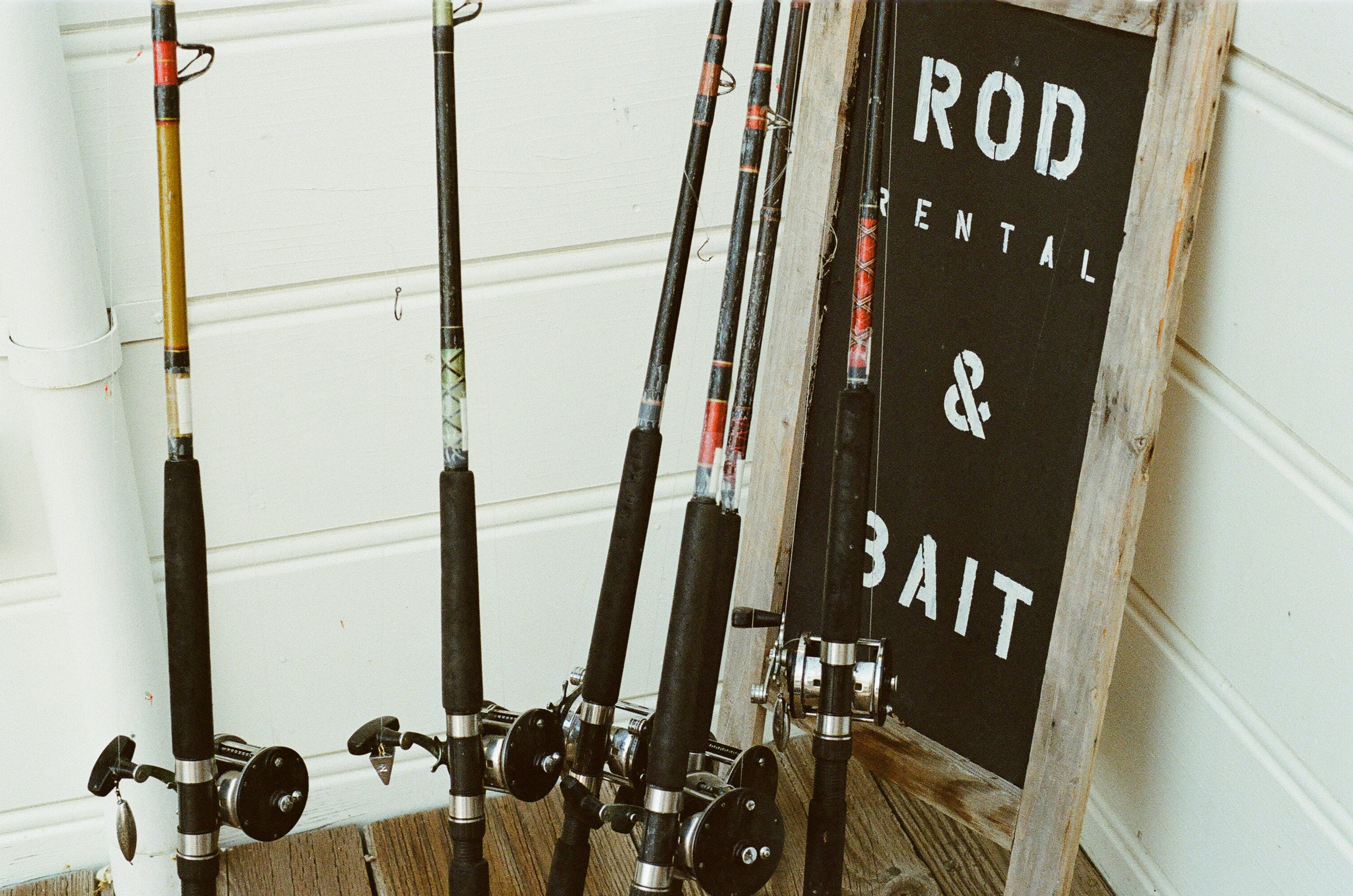 Six Assorted Fishing Rods Beside Rod Rental & Bait Signage