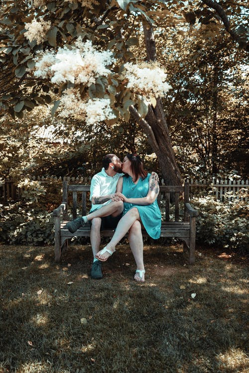 Man and woman kissing while sitting on a bench