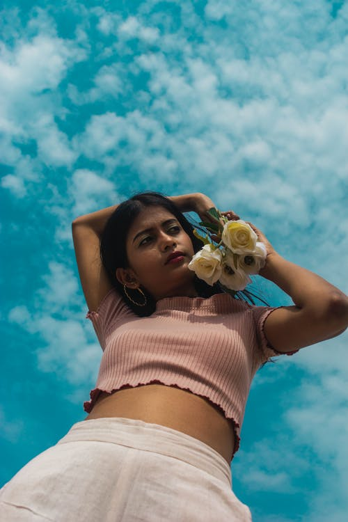 Low Angle Photo of Woman in Peach Short-sleeved Crop Top Holding White Roses Posing Under Blue Sky