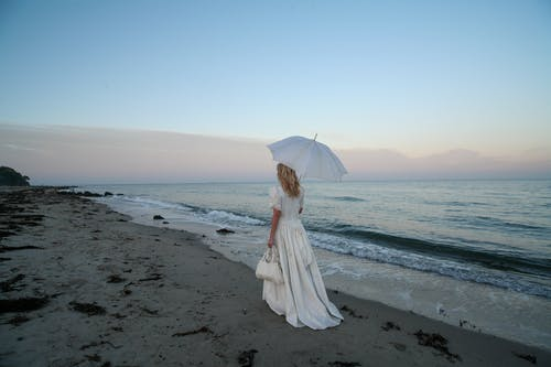 Back View Photo of Woman in White Dress Holding Umbrella and Carrying a Handbag While Walking Alone by the Beach