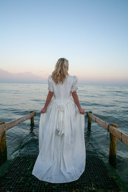 Back View Photo of Woman Standing Near Body of Water