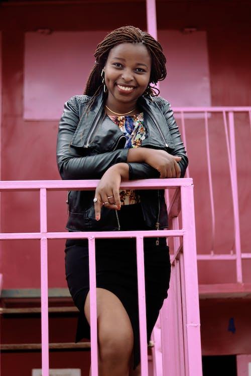 Afrikalı kadın, ayakta, eğik, gülümsemek içeren Ücretsiz stok fotoğraf
