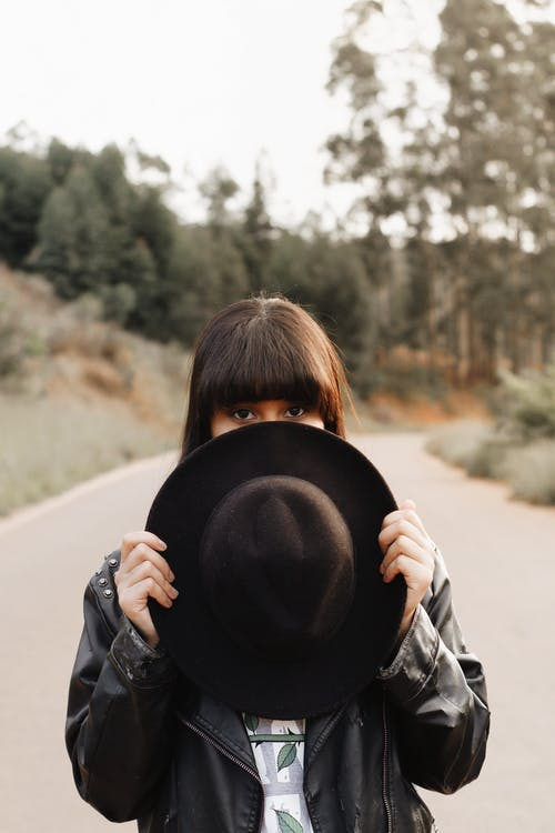 Selective Focus Photo of Woman Standing in the Middle of a Road While Covering Part of Her Face With a Fedora
