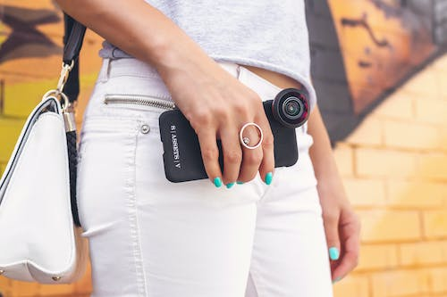 Woman Wearing Grey Shirt And White Denim Jeans Holding Black Smartphone