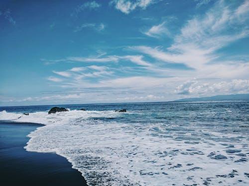 Wavy Seashore Under Blue Sky