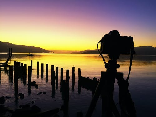 Man Photographing Lake Against Sky during Sunset
