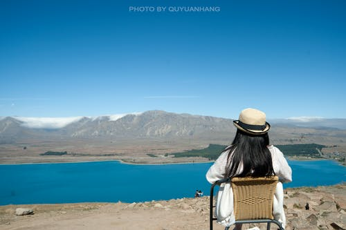 Rear View of Woman Sitting on Shore Against Mountains