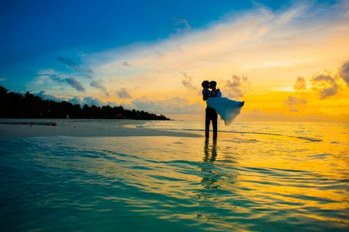 Man carrying a woman on seashore during golden hour