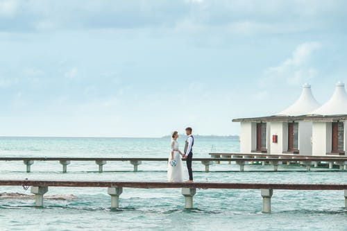 Groom and Bride Standing on Sea Dock