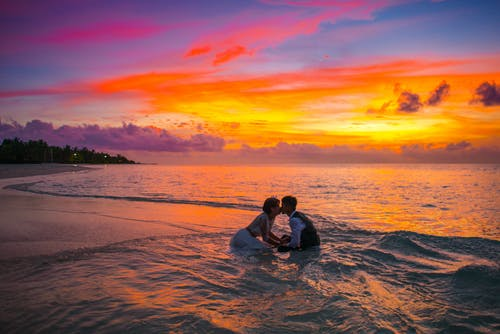 Man and Woman Kissing in the Ocean during Sunset