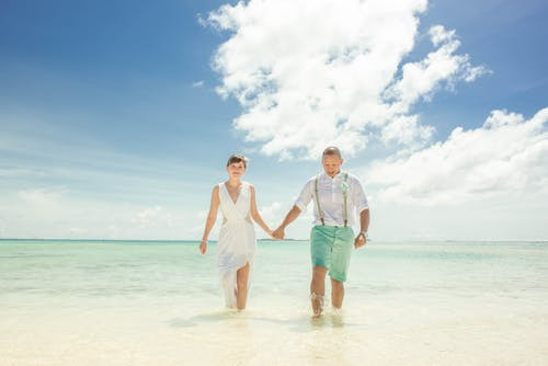 Couple Holding Hands While Walking on Beach