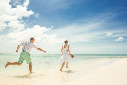 Woman and Man Running on Seashore