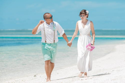 Bride and groom holding hands while walking on seashore