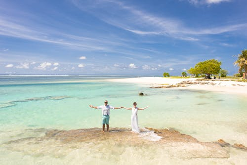 Bride and Groom Standing Beside Body of Water