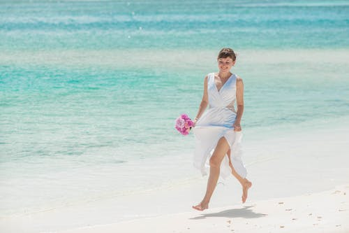 Woman in white dress running on the beach
